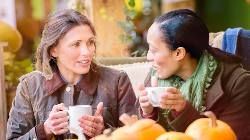 Two women having a conversation over coffee.