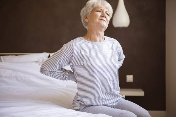 Senior woman uncomfortable bed with back pain.