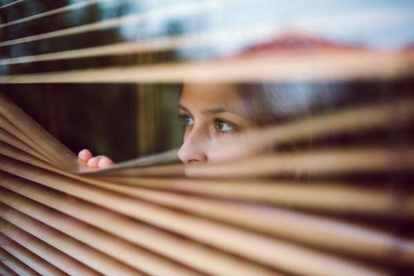 paranoid woman looking through blinds