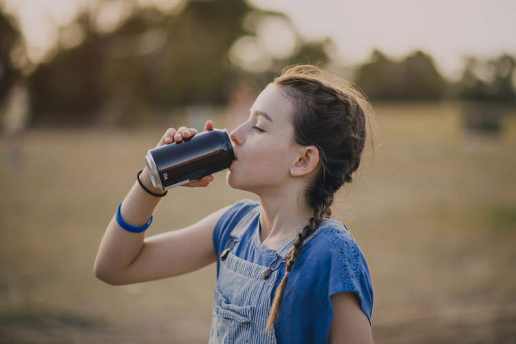 Preteen girl drinking from a soda can outside.