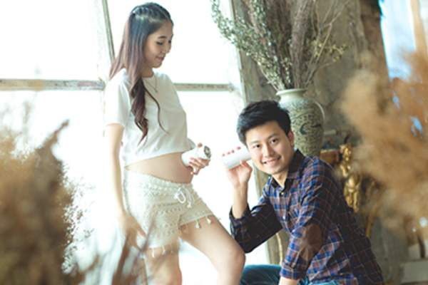 Playful young couple with unborn baby.