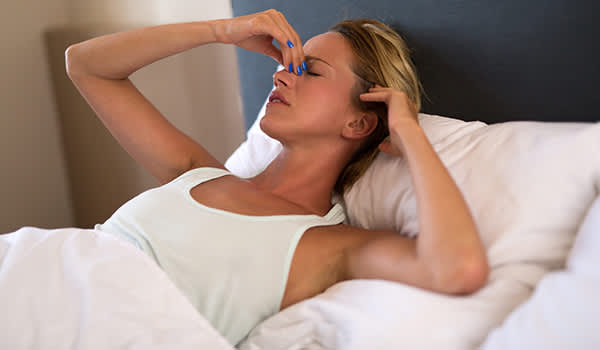 Woman waking up in bed with a migraine.