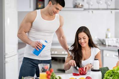 Young man drinking protein supplement while woman cuts vegetables.