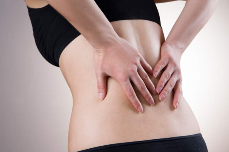 Woman holding lower back with pain from sciatica.