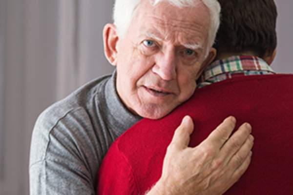 Elderly man being comforted by son image.