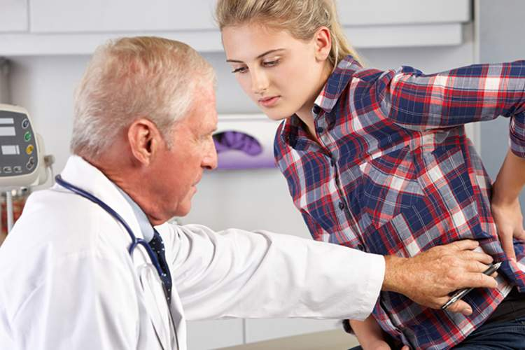 A doctor examines a woman with ankylosing spondylitis.