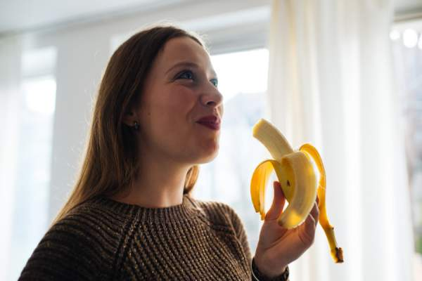Young Fit Woman Peeling and Eating a Ripe Banana
