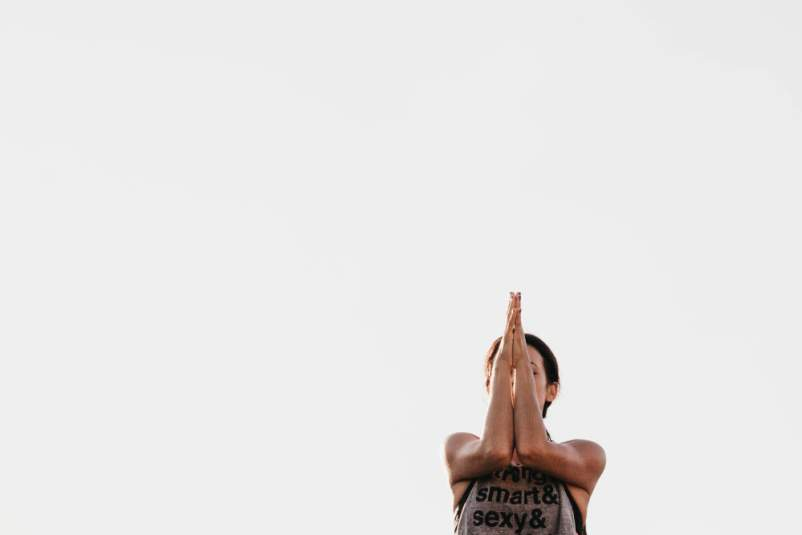 upper body of woman doing prayer hands