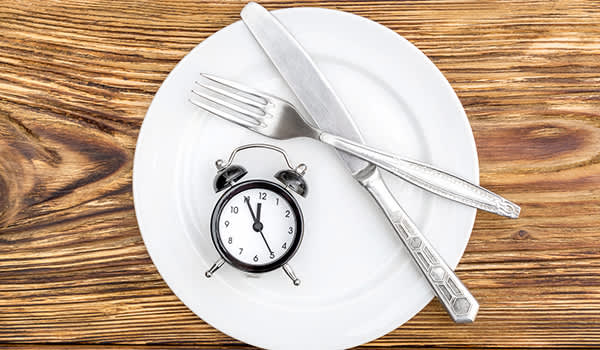 Fasting concept, clock on empy plate.