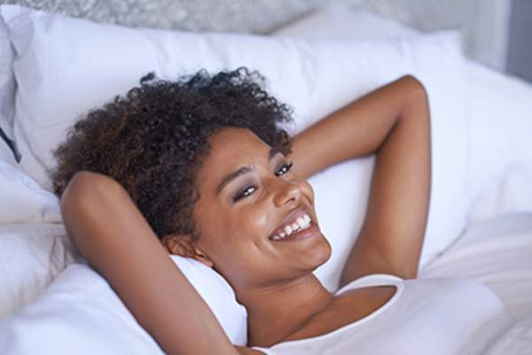 Smiling woman in bed.