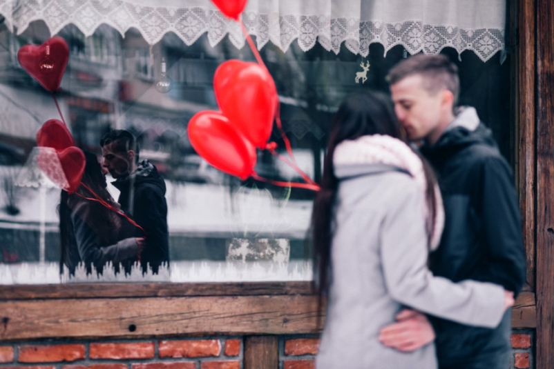 couple kissing with heart balloons