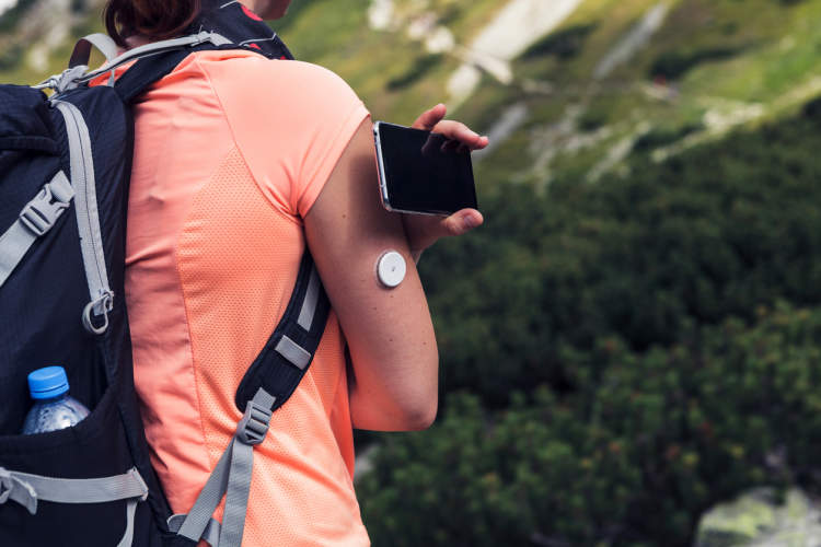 Woman with technical diabetes device hiking.