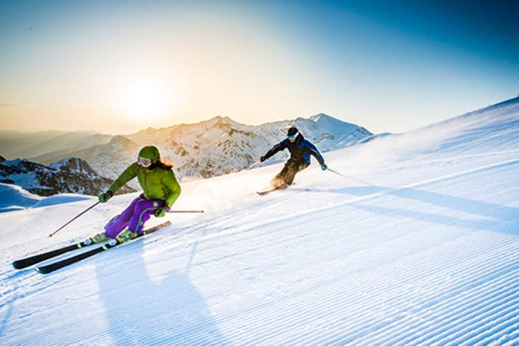 Man and woman skiing downhill.