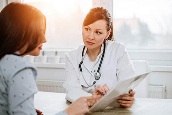 Woman discussing how to handle hyperthyroidism flares with her doctor.