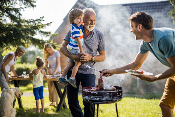 Happy grandfather and grandson talking to young father preparing barbecue in the backyard