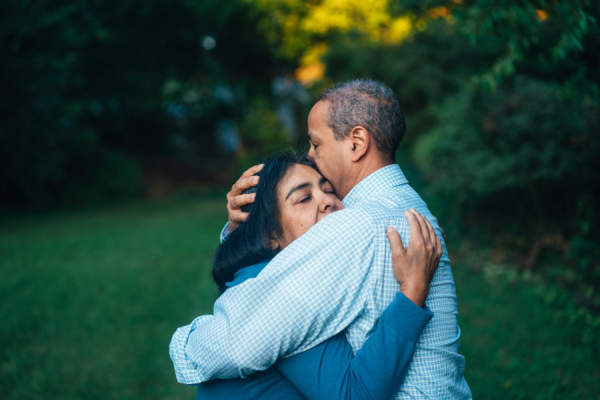 man hugging woman, eyes closed