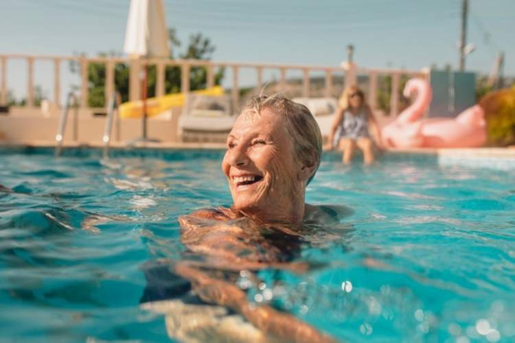 Senior woman smiling in pool