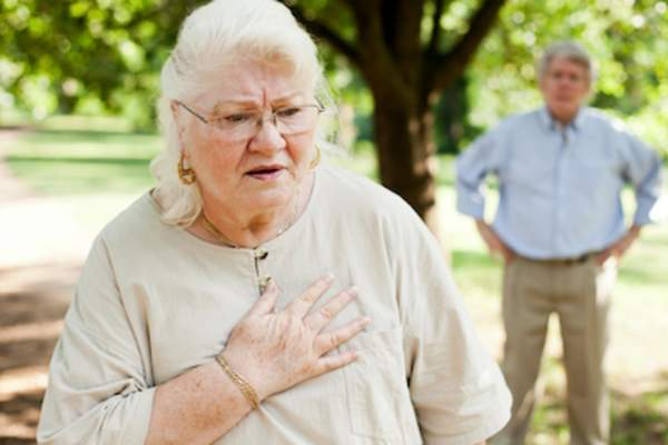 Elderly woman grabbing her chest.