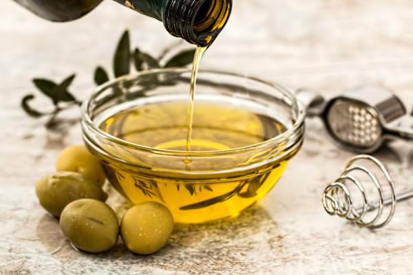 bowl of olive oil next to olives