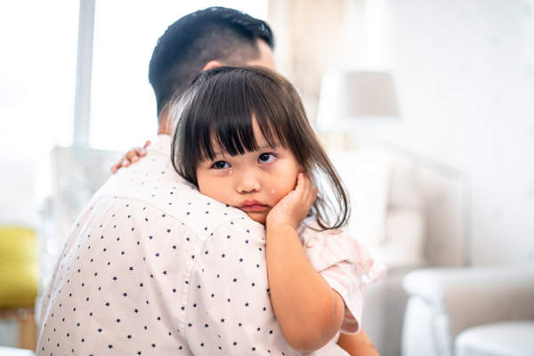 Father hugging crying daughter