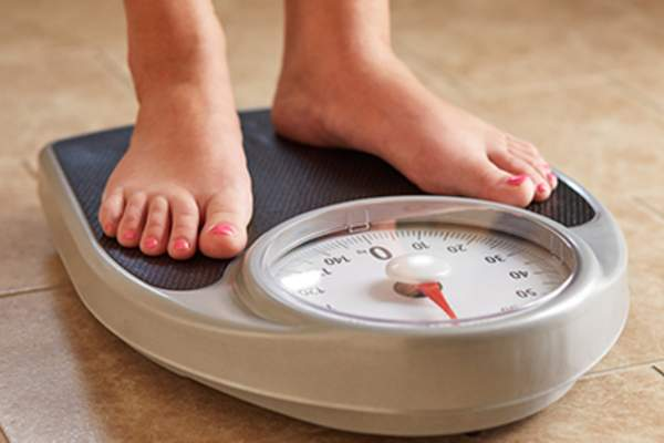 Female feet on weight scale.