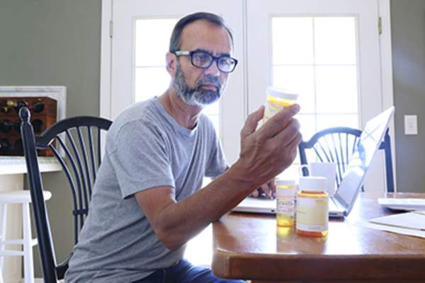 Man looking at prescription drug bottles at home.