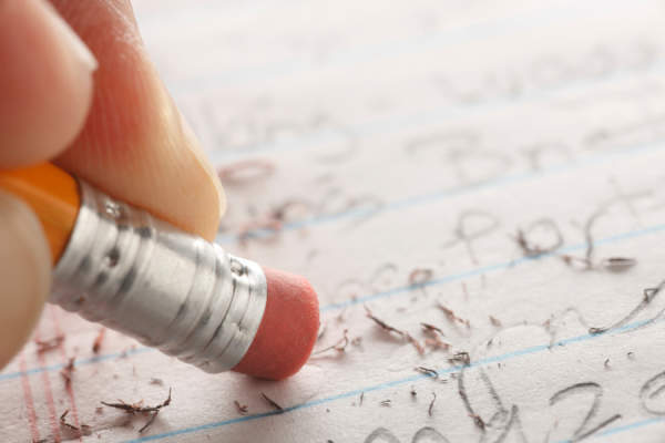 close up of hand erasing pencil