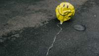 deflated smiley face balloon in the street