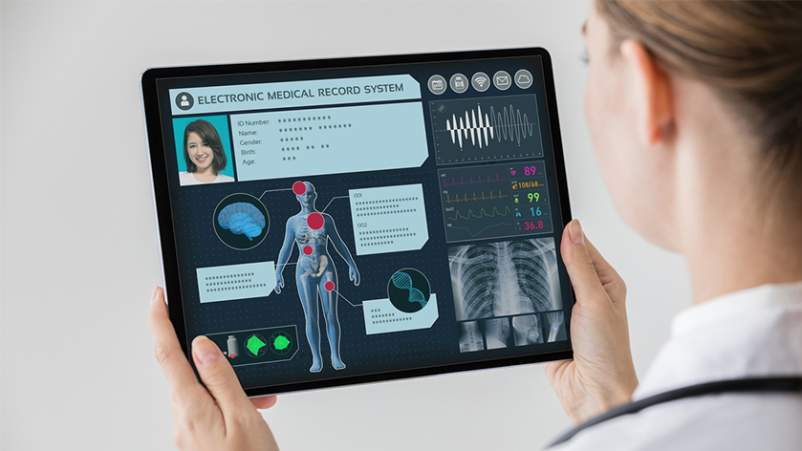 Doctor holding tablet with patient's elecronic health record information.