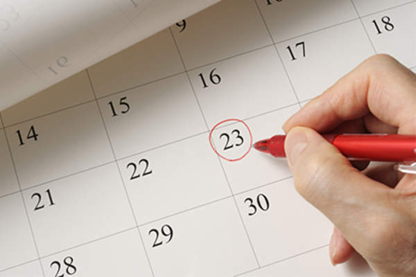 Woman circling a date on the calendar.