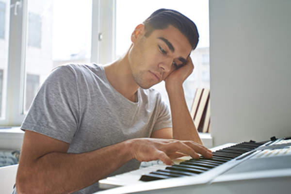 Man uninspired to play music on his keyboard.