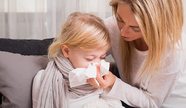 Mother helping sick daughter blow her nose.