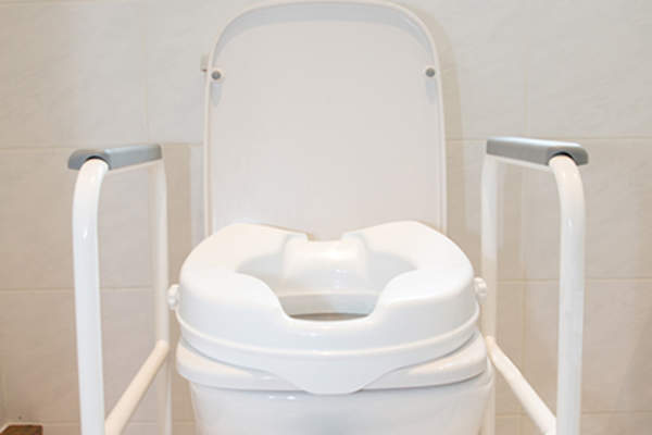 Toilet seat raised for accessibility.