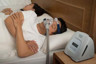Man with sleep apnea wearing using a CPAP machine while he sleeps.