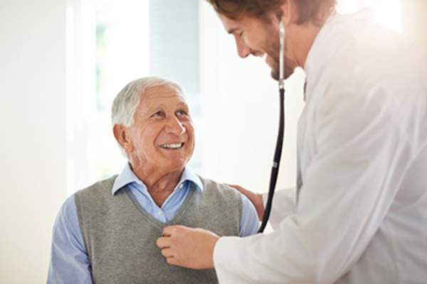 Doctor listening to smiling senior man's heart.