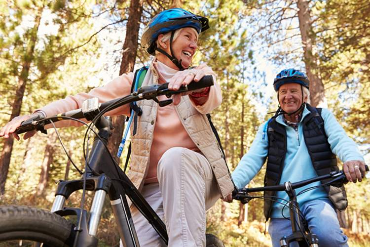 Senior couple riding bikes and smiling at each other.
