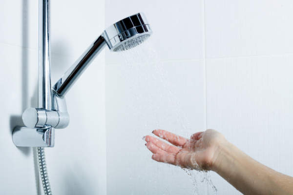 Woman's hand testing water under shower head