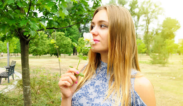 Young woman smelling flower in the park image.