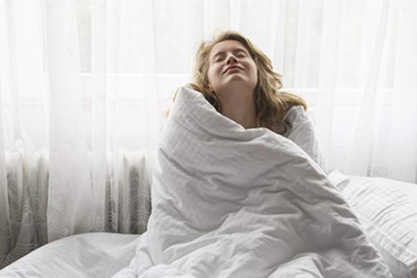 Woman in bed wrapped in a duvet.