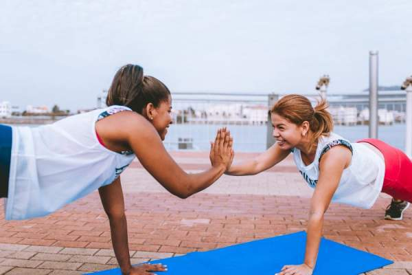 two young women doing planks and high-fiving