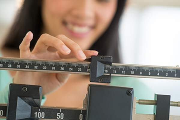 Smiling woman adjusting a weight scale.
