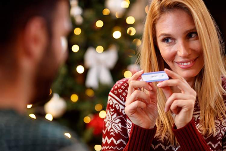 Woman showing man positive pregnancy test during the holidays.