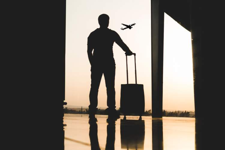 silhouette of man with suitcase looking at plane