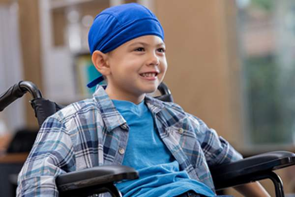 Smiling young boy cancer patient sitting in wheelchair.