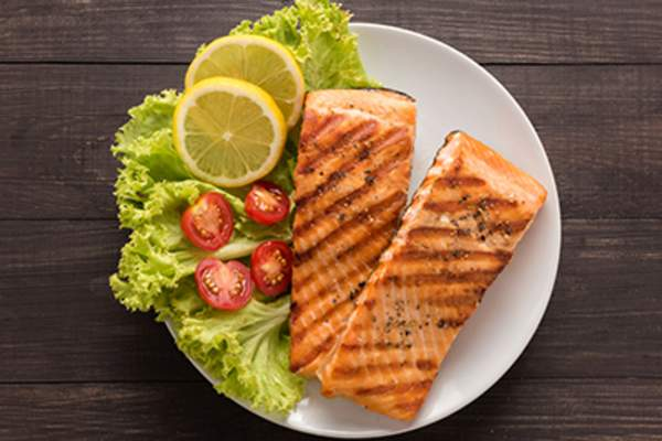 Grilled salmon with lemon, tomato on wooden background