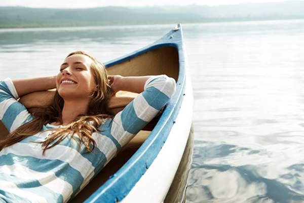 woman relaxing in canoe on vacation image