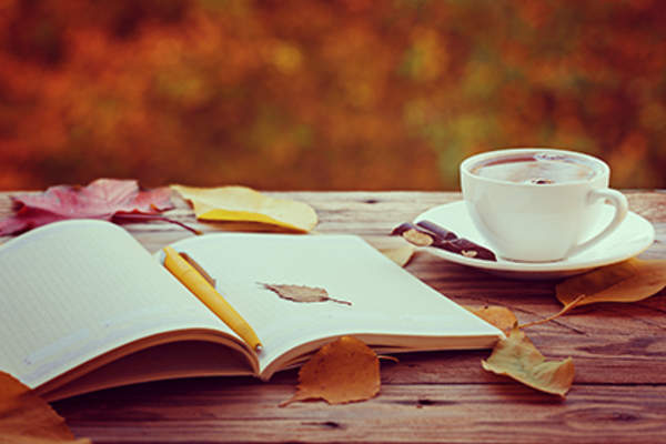 Open journal and a cup of tea covered in fallen autumn leaves.