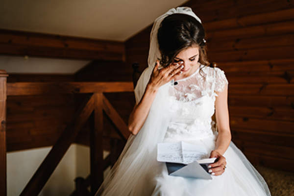 Bride cries as she reads a letter.