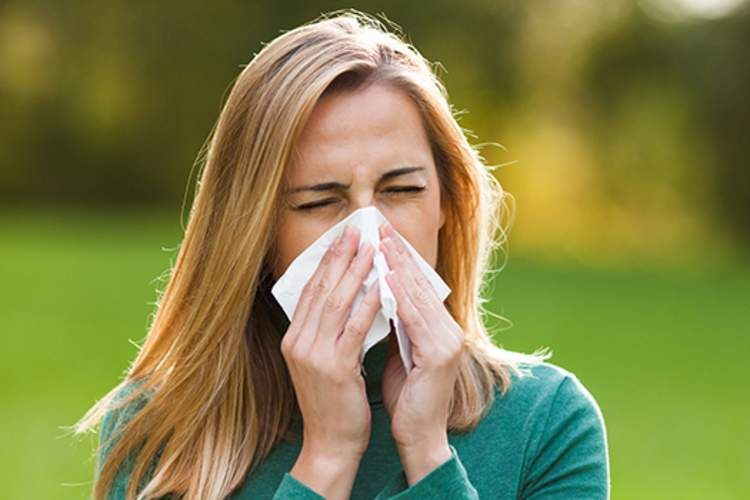 woman blowing nose outside in spring image