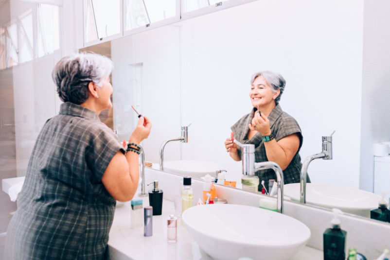 senior woman putting on makeup in mirror